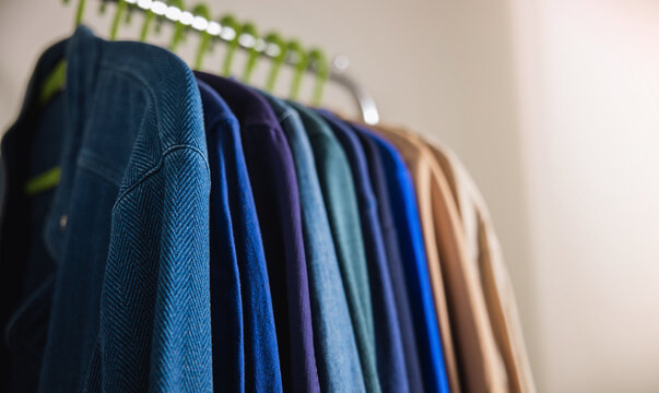 Wardrobe Rack. Men Clothes hanging on Bar by the White Wall. Fashion Lifestyle of a Stylish Man