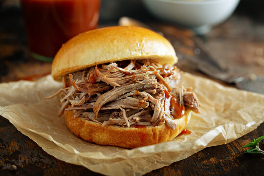 Pulled pork sandwich on a soft brioche bun with bbq sauce and pickles
