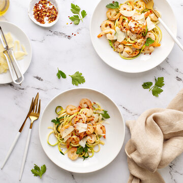 Shrimp and zucchini noodles or zoodles pasta with parmesan and chili flakes plated in white pasta bowls