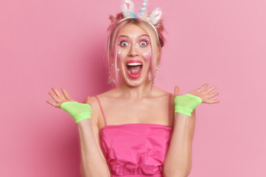 Happy overjoyed woman stares at camera raises hands in sport gloves exclaims emotionally wears unicorn headband and pink dress dresses for carnival or costume party. Photo of slow glow effect