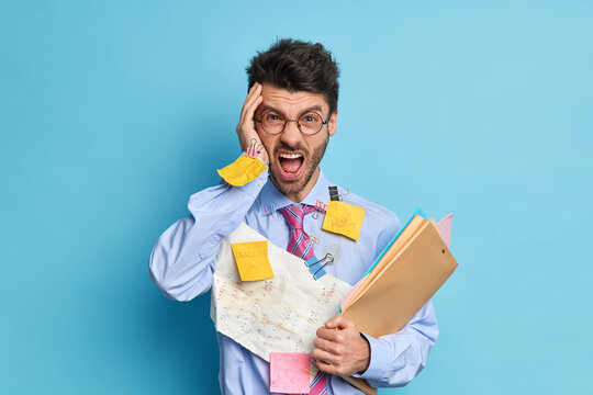 Irritated office worker exclaims with anger being overloaded with paper work holds folders with documentation wears round spectacles isolated over blue background. Angry employee stands indoor