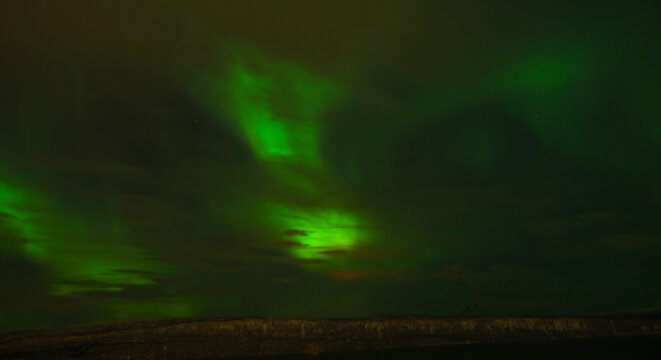 Northern lights Aurora Borealis in the nightsky on Senja Island in the Lofoten Islands of Norway.