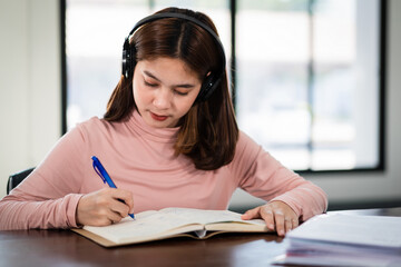 Smiling Asian girl student wears wireless headphones write on the notebook to study language online...