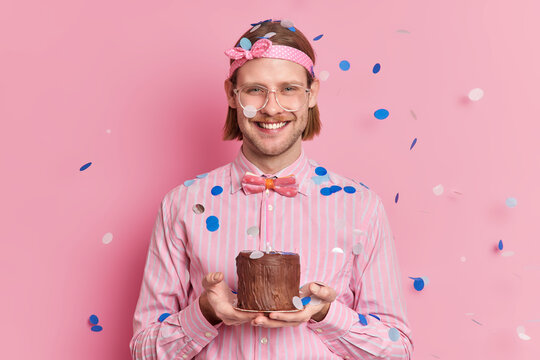 Happy adult man celebrates one year of working in company holds small cake rceieves congratulation from colleagues smiles joyfully wears headband striped shirt and bowtie cofetti falling on him