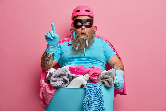 Suprised overweight superhero in helmet tsirt and rubber gloves stands with basin of dirty linen and detergents indicates above poses against pink background. Peope house chores and cleaning concept