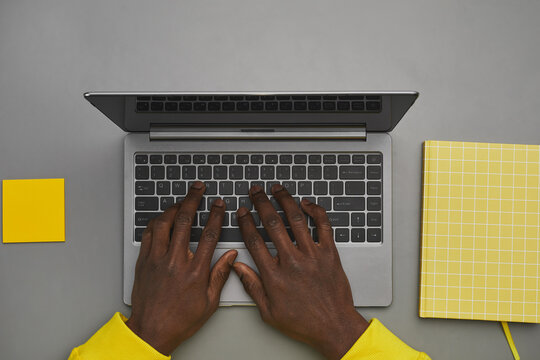 Graphic gray and yellow background of African-American male hands typing on laptop keyboard while working at desk, top down view, copy space