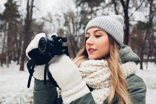 Woman photographer takes pictures of snowy winter park using camera wearing warm clothes. Outdoor activities