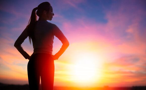 The silhouette of young sporty woman watching the sunset background