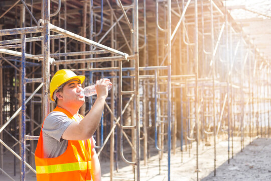 Male engineer drinking water on a summer day on the building under construction