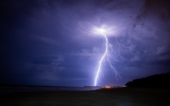 Lightening storm moving in over beach, with city.