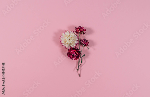 Creative layout made of dried straw flowers isolated on pink background. Flat lay bouquet. Love concept. Mother's day background. Minimal concept flower background.