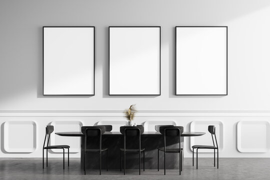 White dining room interior with table and posters