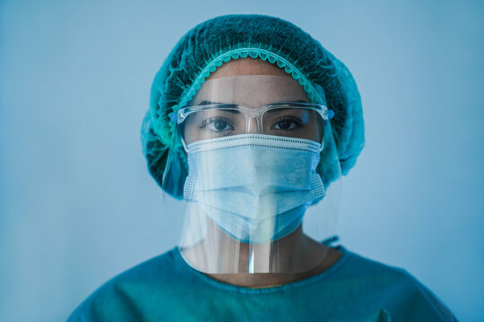 Portrait of young latin nurse work inside hospital during coronavirus period - Woman medical worker on Covid-19 outbreak wearing face protective mask
