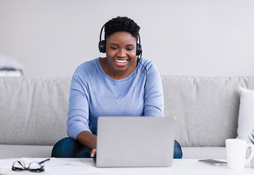 Black woman sitting on couch, having video chat on laptop
