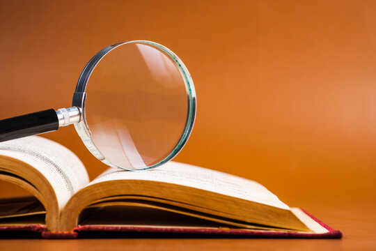 Magnifying glass on opened book