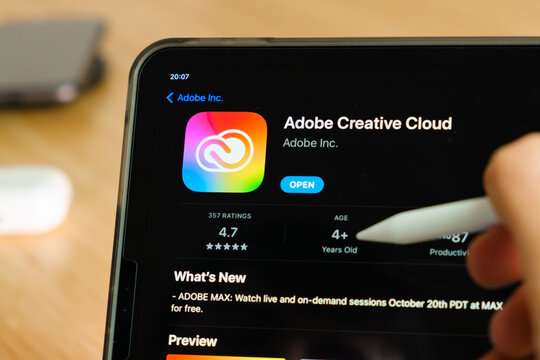 Adobe Creative Cloud logo shown by apple pencil on the iPad Pro tablet screen. Man using application on the tablet. December 2020, San Francisco, USA.
