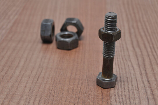 Nuts and bolts covered in rust on a wooden table close up. Engineering, technology, industry