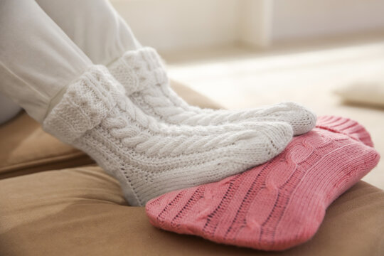 Person warming feet with hot water bottle on sofa, closeup