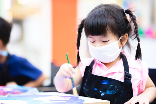 Students girl were concentrating on painting with brushes and watercolor on the canvas. Little Asian child wearing a white cloth mask while learning to color painting. Children aged 3 years old.