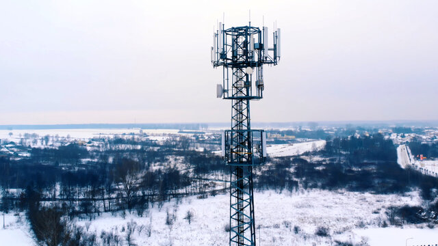 Drone orbiting around 5G antenna covered in snow. . High quality photo