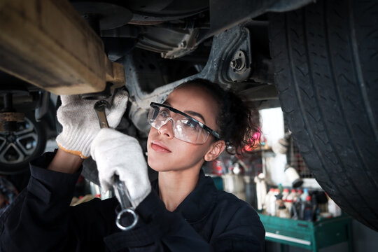 Female auto mechanic work in garage, car service technician woman check and repair customer car at automobile service center, inspecting car under body and suspension system, vehicle repair service sh