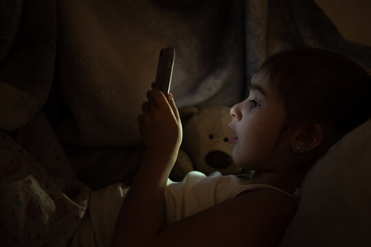 A cute little girl enthusiastically plays on the phone at night in bed instead of sleeping.
