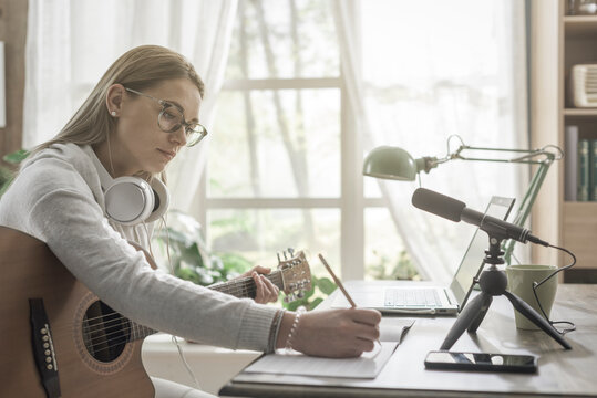 Woman playing guitar and recording her music