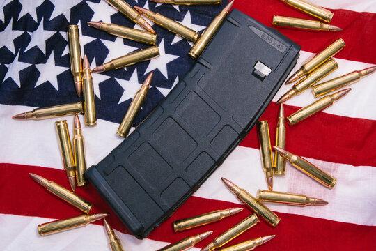 30 round bullet magazine for an AR-15 semi-auto assault rifle guns with .223 Remmington and .556 NATO ammunition behind an American flag