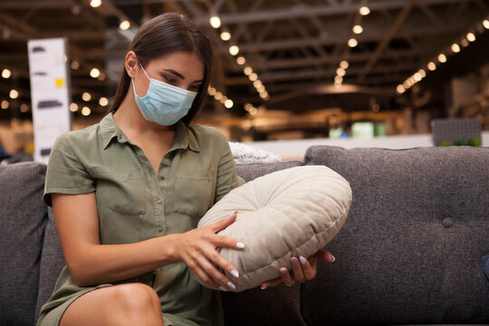 Female customer wearing meidcal mask while shopping at furniture store, examining couch cushion