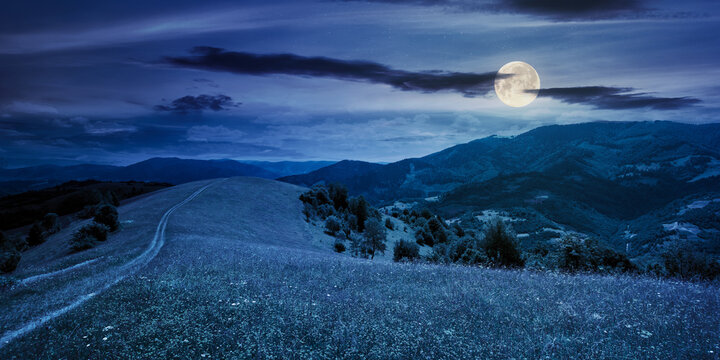 path through the mountain meadow at night. mysterious summer landscape of carpathian countryside in full moon light. fluffy clouds on the blue sky