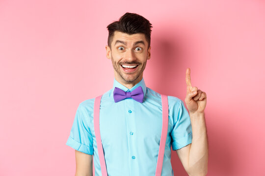 Cheerful caucasian man pitching an idea, raising finger in eureka gesture and smiling, suggesting solution, standing on pink background