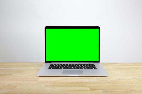 Computer portatile aperto sopra una scrivania di legno con greenscreen sul monitor e sfondo bianco