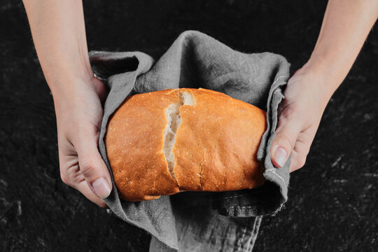 Man hands cutting bread into half on dark table with tablecloth