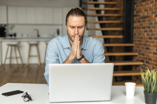 Pensive male freelancer looks at laptop screen anxiously, folded hands in prayer gest, found a mistake in a report, a worried businessman looking for a solution to problems