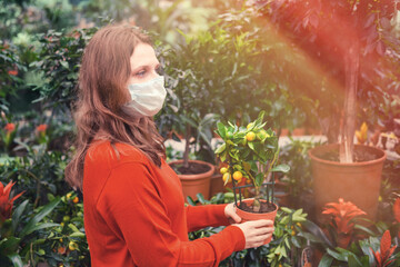 A woman in a medical face mask holds a calamondin citrus tree in a pot against the background of a greenhouse with plants. Home gardening hobby during corona virus quarantine Fototapete