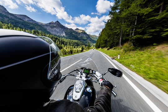 POV of motorbiker holding steering bar, riding in Alps in beautiful dramatic sky. Travel and freedom, outdoor activities