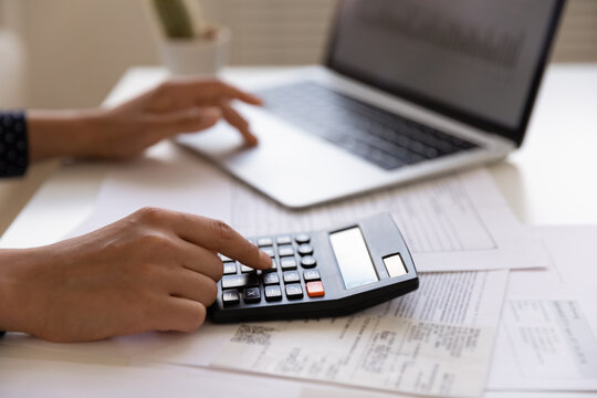 Close up of young female electronic bank client using calculator in paperwork with accounts bills before providing payment online by laptop. Woman hands at work table with papers accounting sum to pay