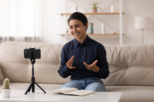 Indian female popular video blogger shoot video content at home make topical review before webcam of phone fixed on tripod. Young hindu lady coach talk on camera of cell device broadcast speech online