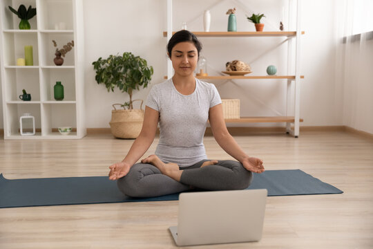 Concentrated indian woman sit on gymnastic mat in lotus pose before laptop screen meditate listen to calm music. Peaceful young hindu lady practice yoga at home learn asanas from online training class