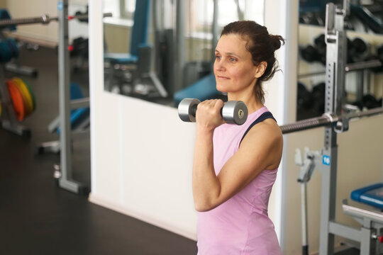 A woman 45 years old is doing fitness in the gym