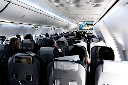 Passenger cabin of commercial aircraft with unrecohnizable travellers seated on their seats during flight.