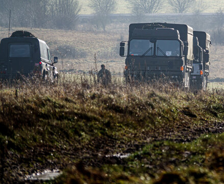 a line of army MAN logistic lorries accompanied by an Army Land Rover Defender 4x4