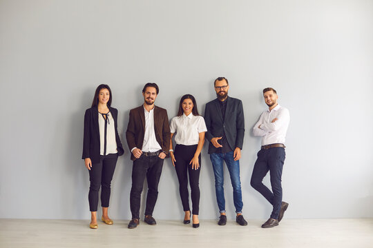 Team of happy young business people in smart casual office wear standing in studio and looking at camera. Group portrait of smiling company employees, startuppers or experienced business coaches