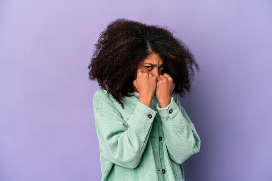 Young african american curly woman isolated on purple background throwing a punch, anger, fighting due to an argument, boxing.