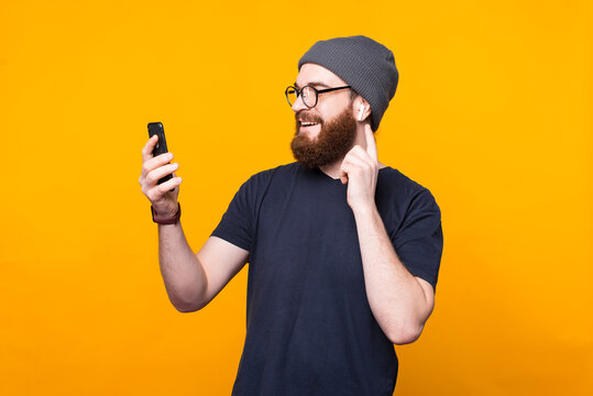 Photo of bearded hipster man looking at smartphone and listening music at earpods.