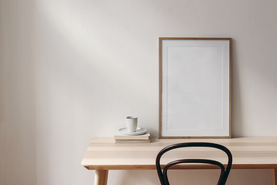 Breakfast still life scene. Cup of coffee, books and empty picture frame mockup on wooden desk, table. Elegant working space, home office concept. Scandinavian interior design. Room in sunlight.