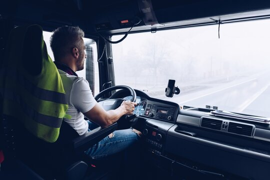 Handsome driver at the wheel of a truck at work. Work of a lorry driver.