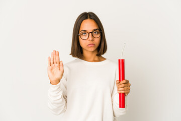 Young hispanic mixed race woman holding a dynamite standing with outstretched hand showing stop sign, preventing you.