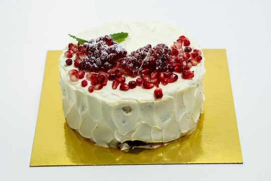 Cake sprinkled with pomegranate berries. Cake on white backgroun