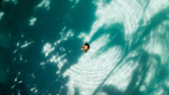 Aerial shot of woman at the pool covering the face with her hands